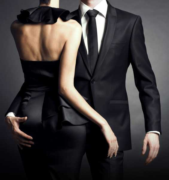 Stylish man in a suit and a girl in an evening black dress