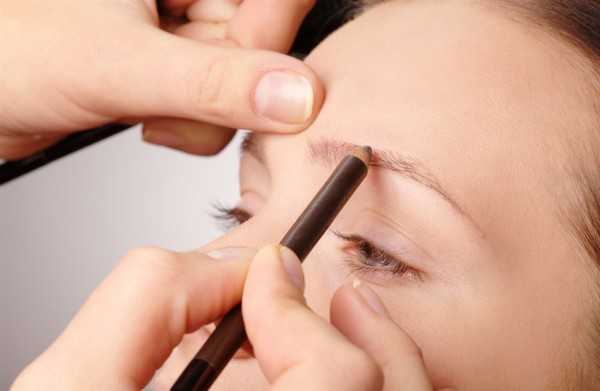 Stylist is penciling eyebrow for young girl
