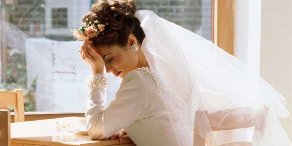 Bride sitting alone at table, head in hands